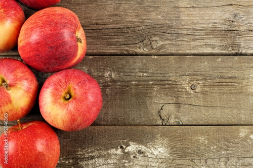 Freshly harvested apples, side border on rustic aged wood background Poster