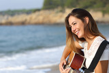 Fototapety Beautiful guitarist woman playing guitar on the beach