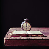 old alarm clock and book on a rustic wooden table
