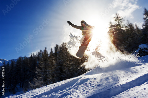 Powerful image of a snowboarder jumping over a kicker in the backcountry powder Poster