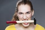 enraged 20s woman biting hammer for aggressive handwork or DIY poster