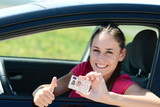 Fototapety cheerful and happy young woman in her car showing her new driving license
