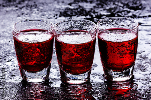 Vodka shot glass on wet black surface. - 92250111
