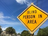 Road sign informing drivers about a blid person in the area.