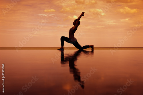 Poster silhouette Reflextion of low lunge in Yoga pose with sunset background