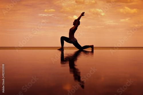 Poster Silhouette Reflextion von niedrigen Longe in Yoga-Pose mit Sonnenuntergang Hinte