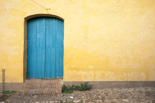 Sticker Simple brightly painted blue door in a smooth yellow ochre stucco wall on a cobblestone street in Trinidad, Cuba