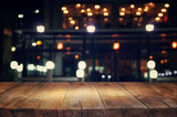 Fototapety image of wooden table in front of abstract blurred background of resturant lights