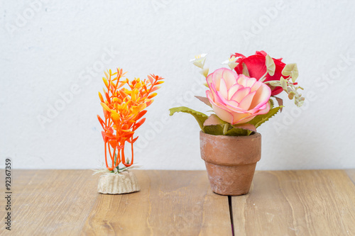 plastic flower in pot and plastic plant on wooden board