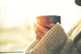hands holding hot cup of coffee or tea in morning sunlight