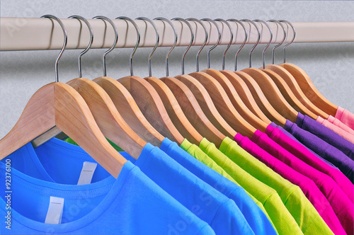Poster Multicolored women's t-shirts hang on wooden hangers.
