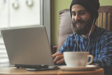 Fototapety Young hipster man working on laptop in coffee shop
