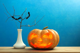 terrible pumpkin on a wooden table with a vase and twigs