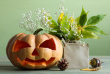 pumpkin with leaves and chestnuts and a vase with dried flowers and leaves on wooden table on green background