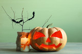 pumpkin vase and branch next to a candle on a wooden table