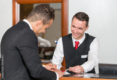 Receptionist at hotel reception assisting a guest