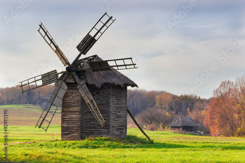 Old windmill on a background of forest and sky - 92493398