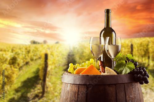 Fototapeta White wine bottle and glass on wodden keg