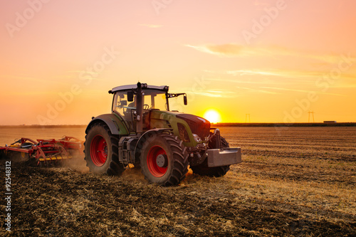Plagát Tractor on the barley field by sunset.