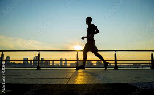 Naklejka Silhouette of jogger running at sunset in front of the city skyline
