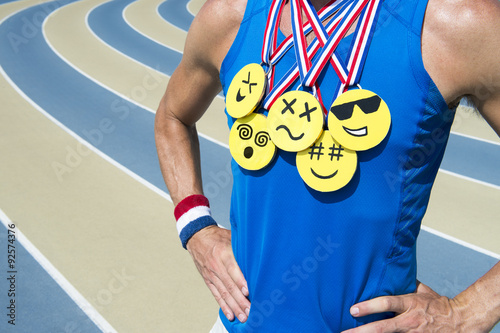 Athlete standing at running track wearing gold medals with bright yellow emoji f Poster