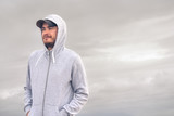 Young man wearing a hoodie and a baseball cap with a cloudy day