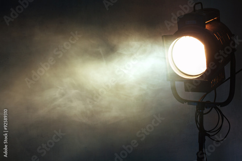 Poster theater spot light with smoke against grunge wall