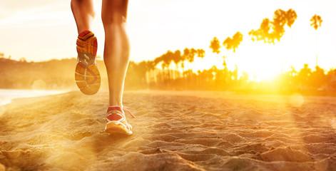 Fototapeta biegacz na plaży o zachodzie słońca