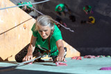 Aged Woman Climbing Wall