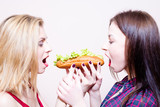 Picture of 2 hungry beautiful girls having fun eating together