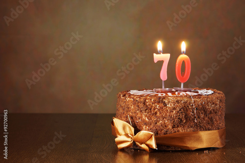 Poster Birthday chocolate cake with burning candles as a number seventy on brown backgr