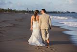 Wedding / Groom and bride walking on the beach
