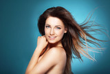 Fototapety Beautiful young woman with long brown flying hair on  blue backg