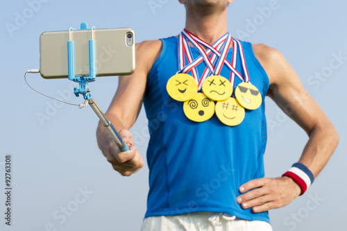 Athlete taking selfie wearing gold medals with bright yellow emoji faces with sm Poster