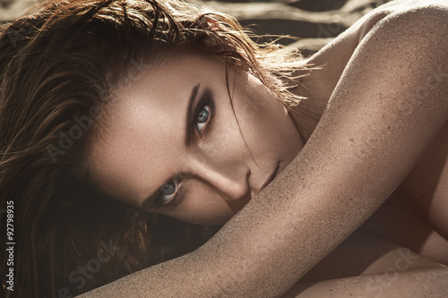 Beautiful woman lying on the sand Poster