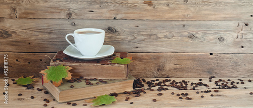 cup of coffee on the books in autumn maple leaves