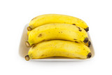 Heap of yellow ripe cavendish bananas in a white plate. They are isolated on white background in studio. poster