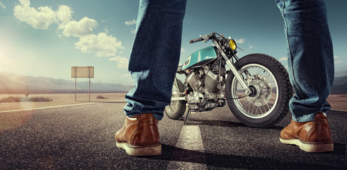 Sport. Biker standing near the motorcycle on an empty road at sunny day. Close view on legs