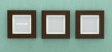 Square wooden picture frames on green wall