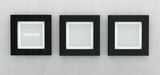Square black wooden picture frames on grey wall