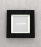 Square black wooden picture frame on grey wall