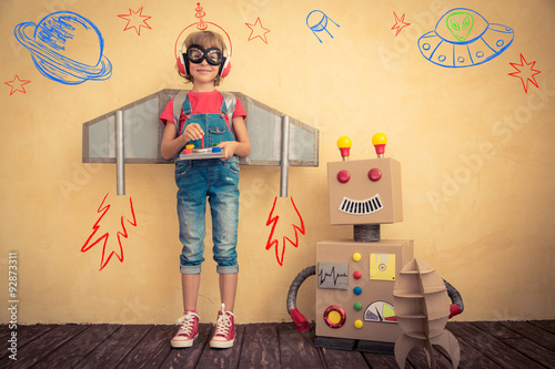Poster Happy kid playing with toy robot