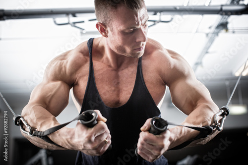 Bodybuilder doing butterfly on cable pull Poster