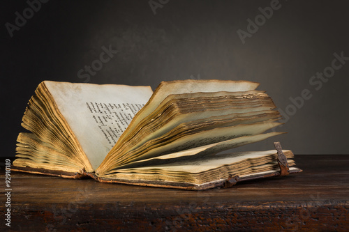 Old open book on a table.