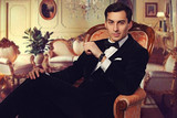 Confident successful young handsome man businessman in elegant suit with bow tie sitting on vintage armchair in luxurious living room. Manhood. Male beauty. Fashion model studio shot. Italian style.  poster
