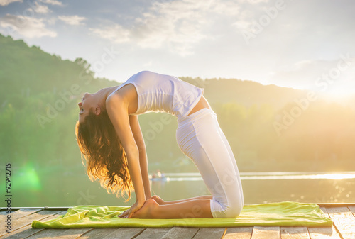 Stampa su Tela Woman doing yoga on the lake - relaxing in nature