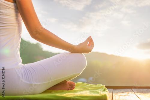 Stampa su Tela Woman doing yoga on the shore - half figure sitting