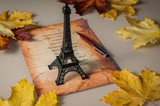 statuette of Eiffel tower, yellow leaves, the verse in French, a poster
