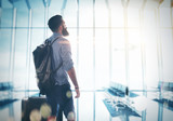 Bearded man standing at the airport hall with a suitcase