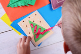 Close up on child making Christmas Tree from colored paper.   Kids Art, Art Projects, Handmade New Year decorations